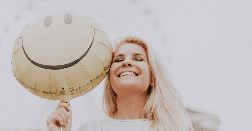woman smiling holding happy balloon