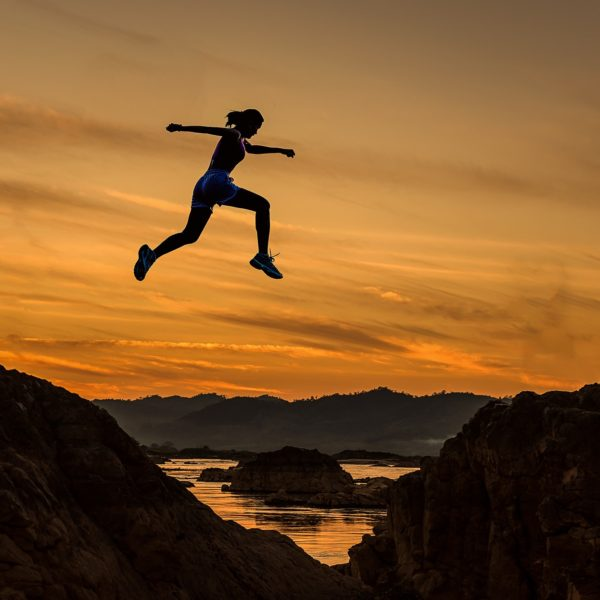 person leaping over cliffs
